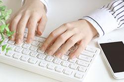 パソコンを打つ女性の手の写真