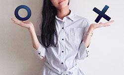丸とバツのオブジェを持つ女性の写真